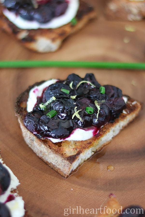 Close up of a blueberry goat cheese crostini.