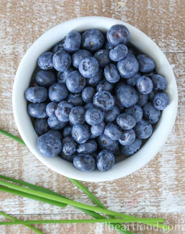 Bowl of fresh blueberries alongside some fresh chive sprigs.