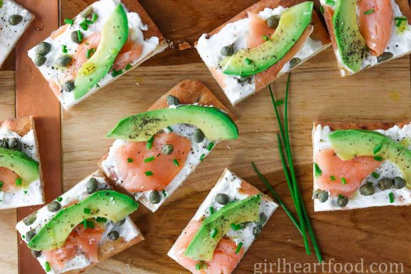Avocado and smoked salmon flatbread appetizer on a wooden board alongside some fresh chive.