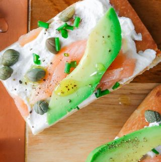 Avocado and smoked salmon flatbread appetizer with goat cheese, capers and chives.