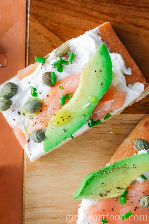 An overhead shot of an avocado and smoked salmon flatbread appetizer.