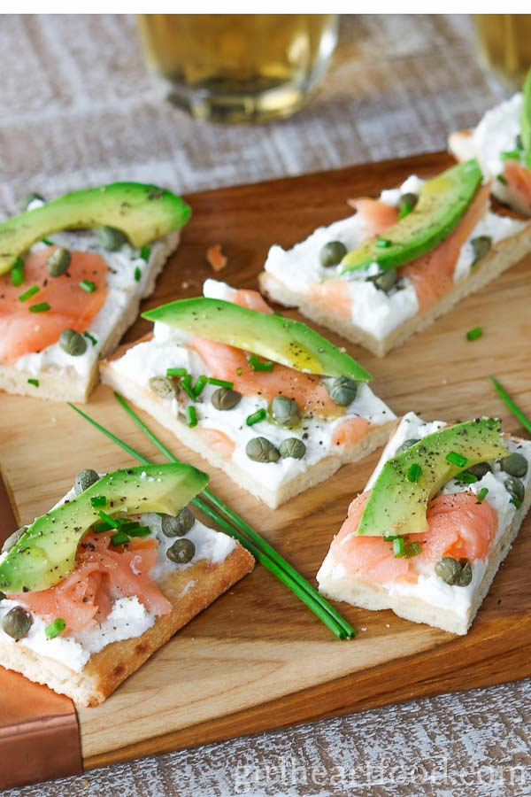 Avocado and smoked salmon flatbread appetizers on a wooden board.