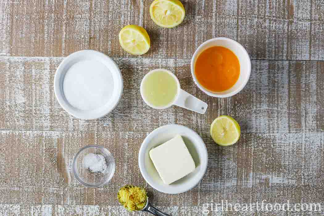 Ingredients for the best lemon curd recipe on a wooden board.