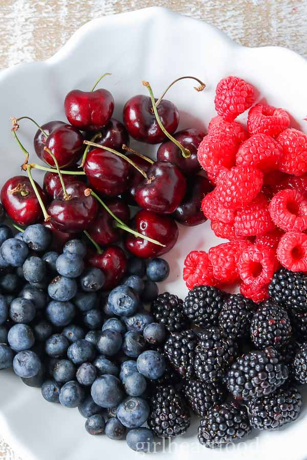 An overhead shot of fresh berries and cherries in a white bowl.