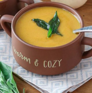 A bowl of healthy butternut squash soup with crispy sage.