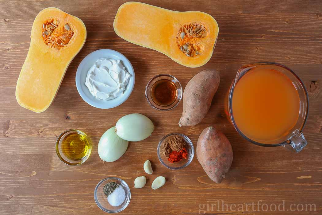 Ingredients for roasted butternut squash and sweet potato soup on a wooden board.