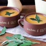Two bowls of butternut squash and sweet potato soup with crispy sage.