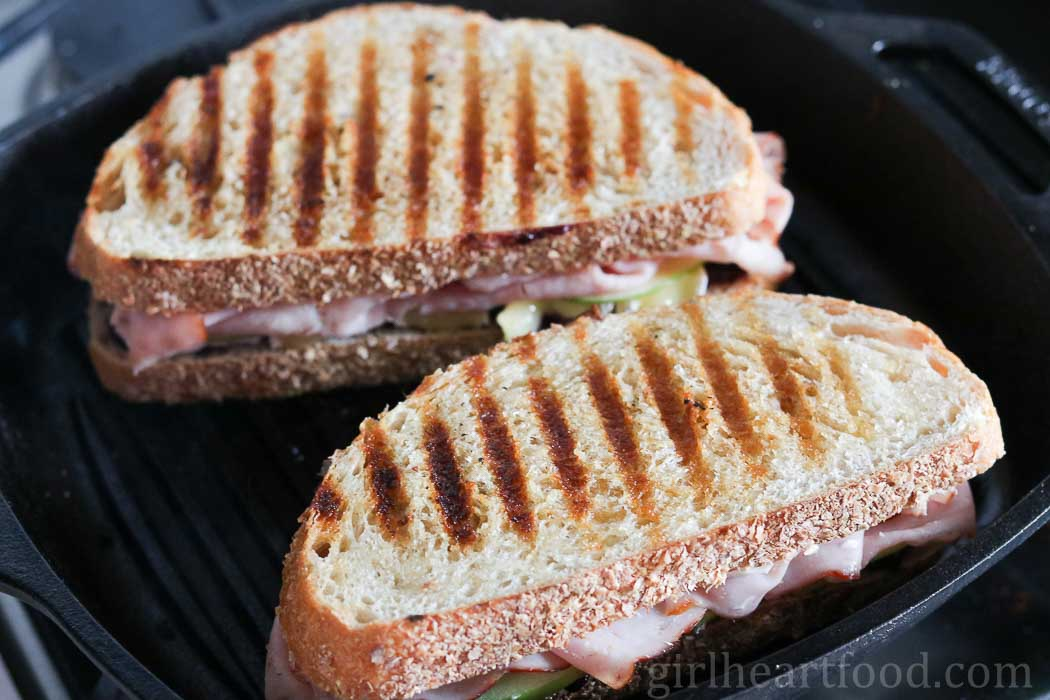 Grilled ham and brie sandwich in a griddle pan.