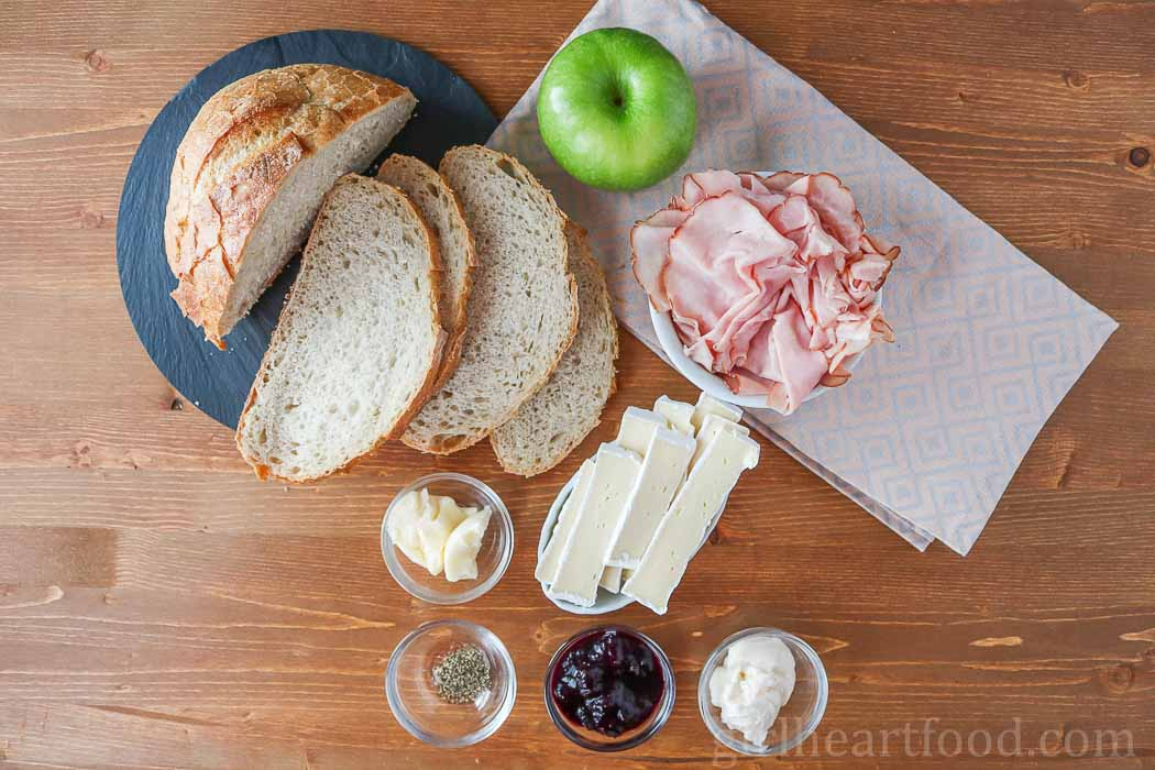 Ingredients for a ham and brie sandwich recipe on a wooden board.