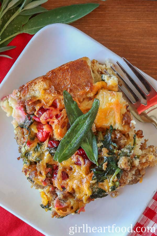 An overhead shot of a serving of breakfast strata garnished with crispy sage.