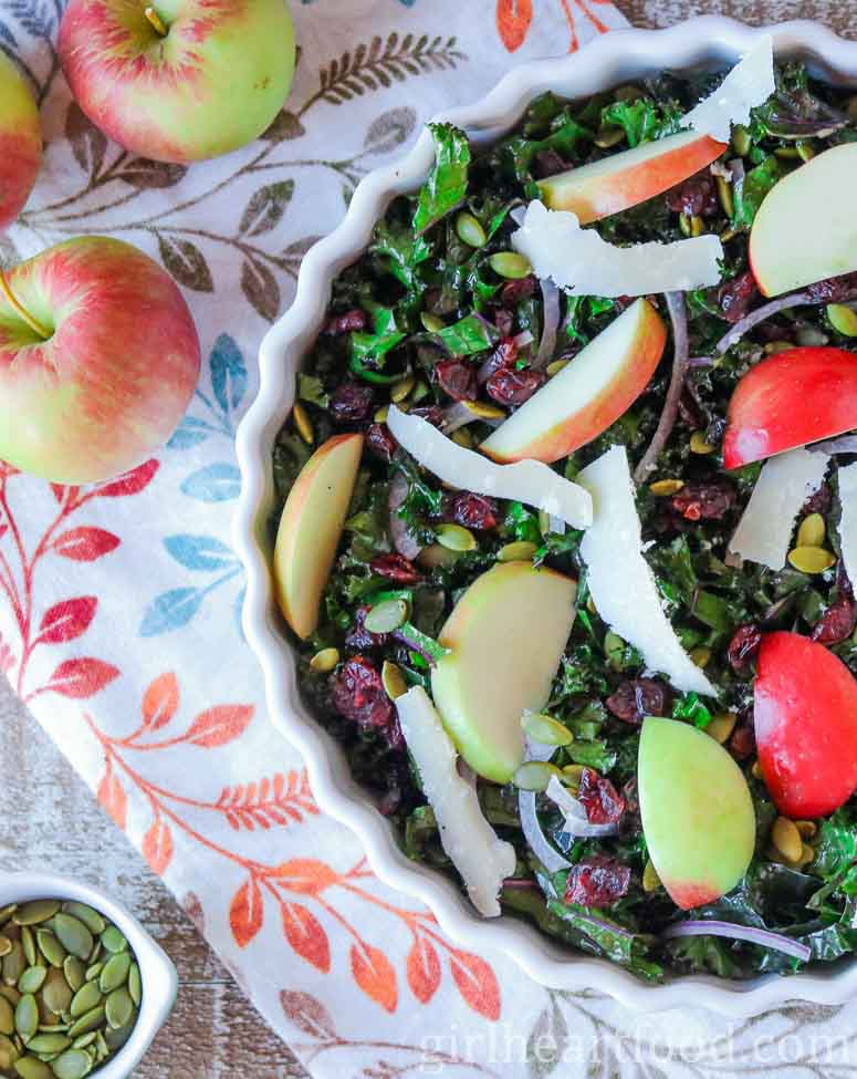 Left-hand side of a bowl of kale and apple salad, next to apples and dish of pumpkin seeds.