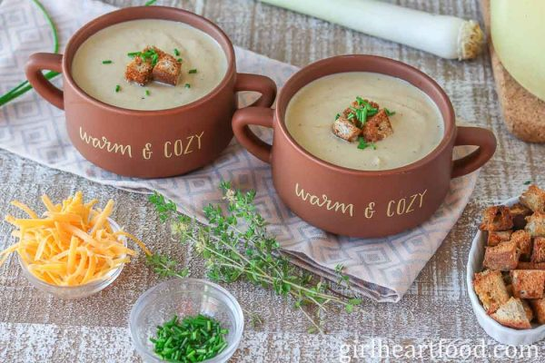 Two bowls of cauliflower leek soup garnished with croutons and chives.