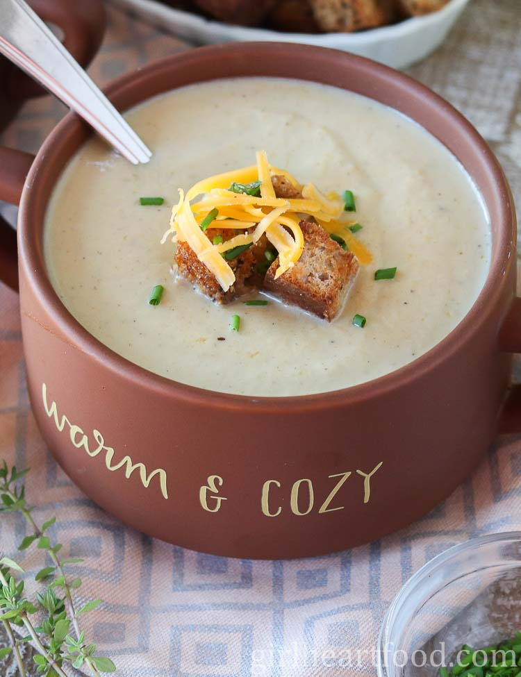 A bowl of cauliflower leek soup garnished with croutons, chives and cheddar.