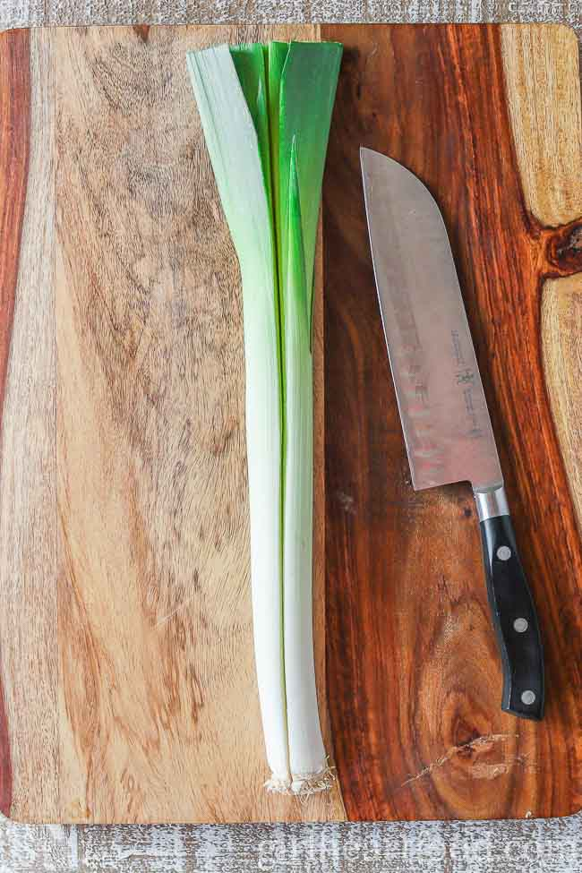 A leek on a wooden board alongside a knife.