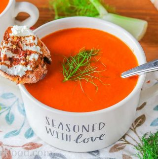 A bowl of roasted red pepper and tomato soup with fennel garnished with fennel fronds and goat cheese crostini.