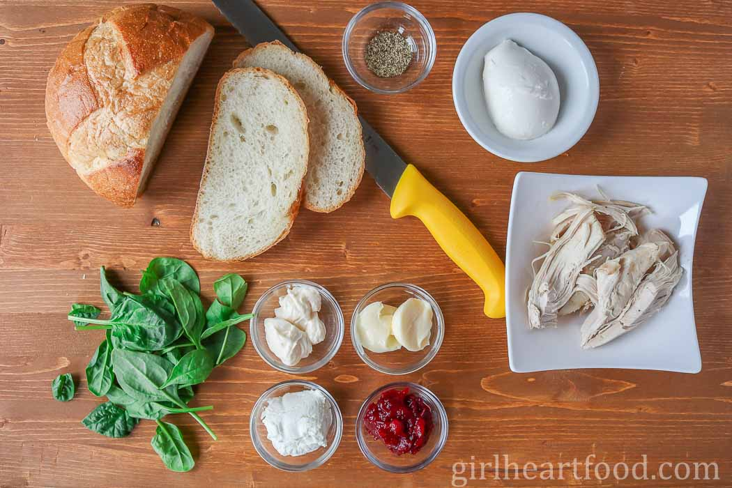 Ingredients for a turkey cranberry sandwich on a wooden board.