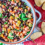 An overhead shot of a large dish of black bean and corn salsa alongside some tortilla chips.