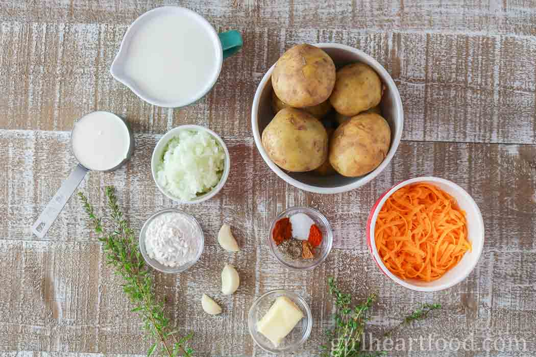 Ingredients for homemade scalloped potatoes with cream on a wooden board.