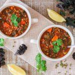 Two bowls of mung bean soup alongside kale, lemon, cilantro and mung beans.