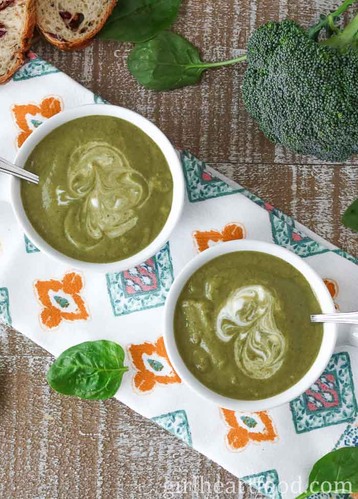 Overhead shot of two bowls of broccoli spinach soup alongside spinach and a head of broccoli.