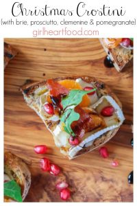 An overhead shot of a holiday crostini recipe on a wooden board alongside some pomegranate.