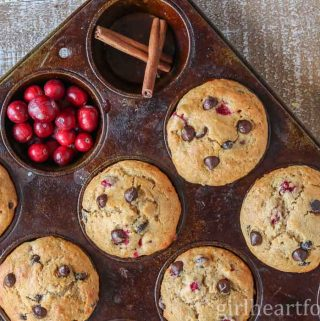 Pan of cranberry orange chocolate chip muffins next to cranberries, cinnamon, and orange.