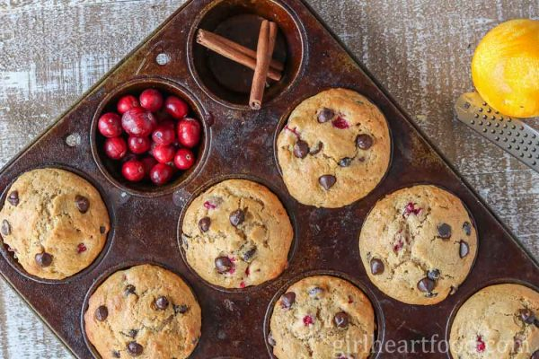 An overhead shot of a pan of cranberry orange muffins with chocolate chips alongside cranberries, cinnamon sticks and an orange.