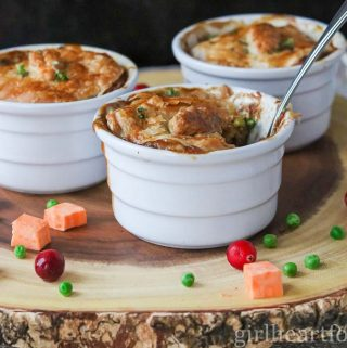 Individual chicken pot pies on a board alongside chopped sweet potato, peas and cranberries.