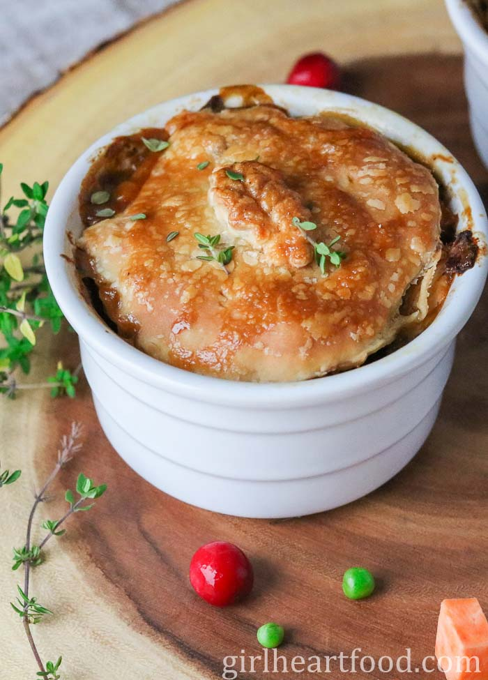 Individual chicken pot pie recipe with puff pastry in a white dish on a wooden platter.