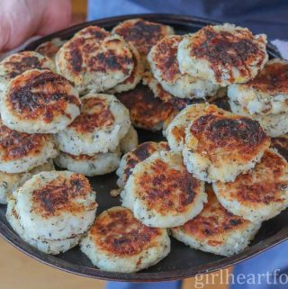 Someone holding up a large tray of cooked traditional Newfoundland fish cakes.