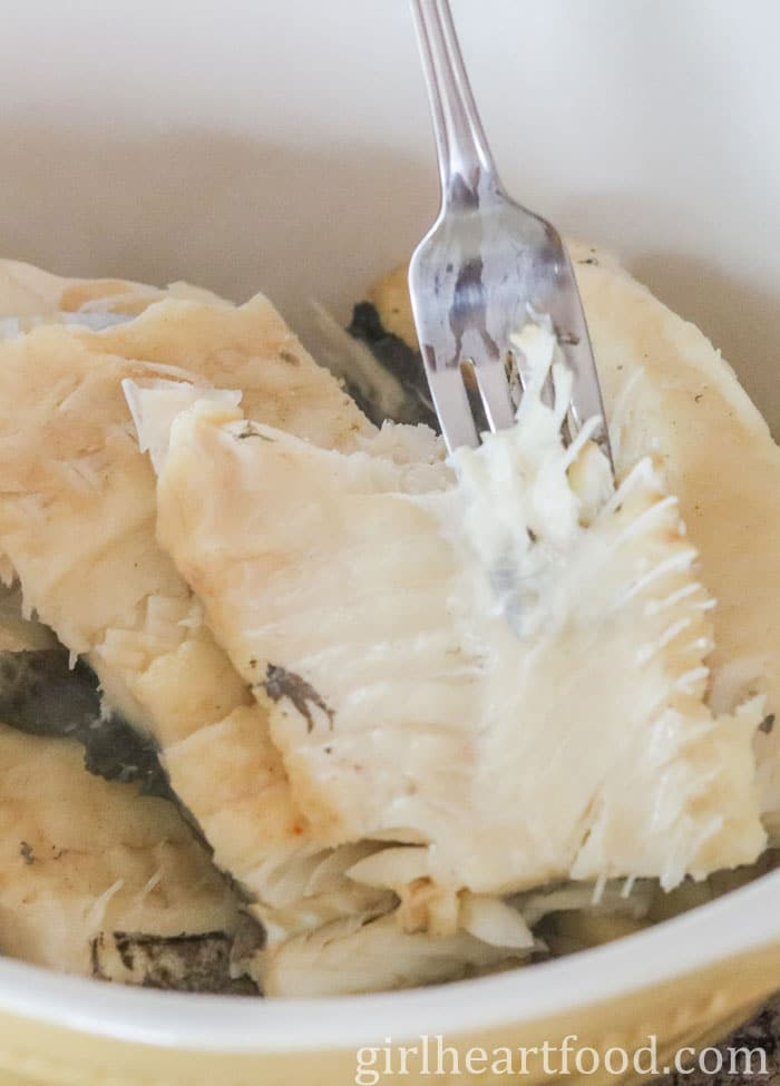 A bowl of salt cod fish with a fork into it, removing bones.
