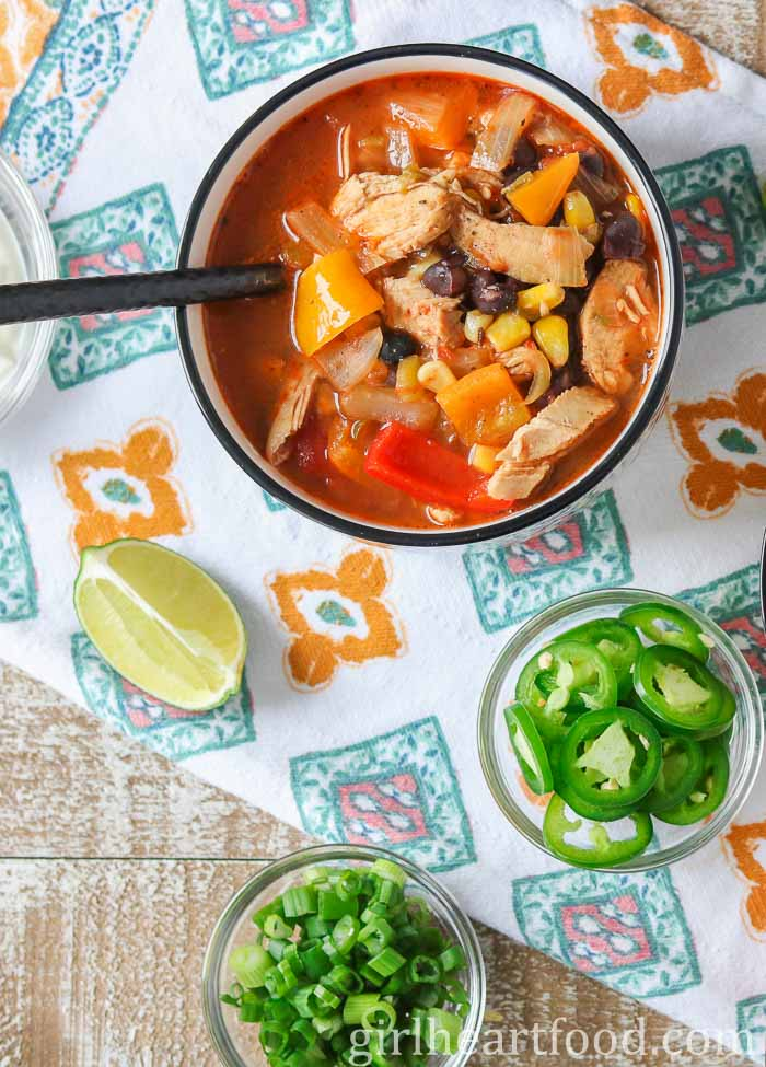 An overhead shot of a bowl of stovetop chicken taco soup alongside some garnish.