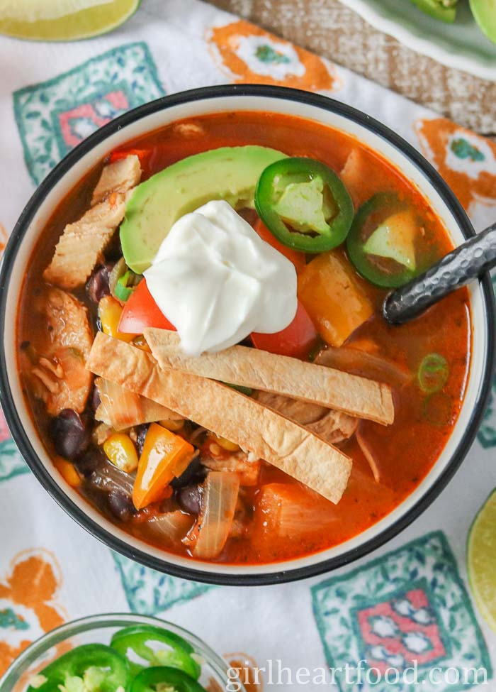 An overhead shot of a bowl of lighter chicken taco soup garnished with tortilla strips, hot pepper, avocado, onion and yogurt.