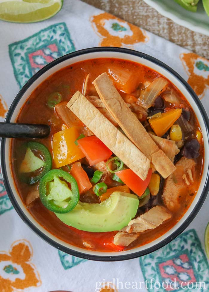 Bowl of chicken taco soup garnished with toppings.