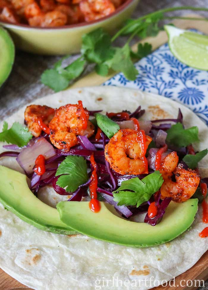 A close up shot of a shrimp taco garnished with slaw, avocado, cilantro and sriracha.