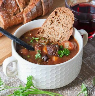 Bowl of moose meat vegetable stew with a piece of bread dunked into it.