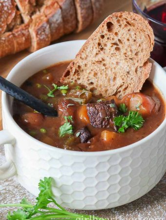 A bowl of moose stew with a piece of bread dunked in.