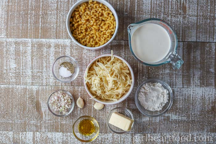 Ingredients for a macaroni and cheese recipe on a wooden board.