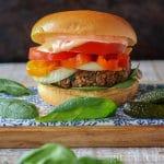 A garnished lentil mushroom burger alongside some baby spinach.