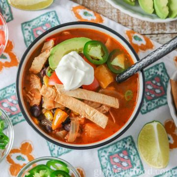 Bowl of chicken taco soup garnished with toppings and dollop of yogurt.