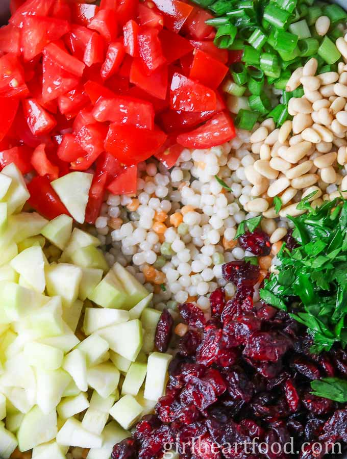 An overhead close up shot of the ingredients for a cold couscous salad not yet mixed together.