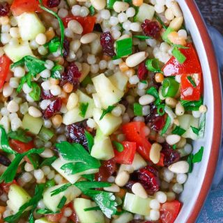 Bowl of cold pearl couscous salad garnished with parsley.