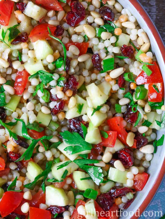 An overhead close up shot of pearl couscous salad garnished with parsley.