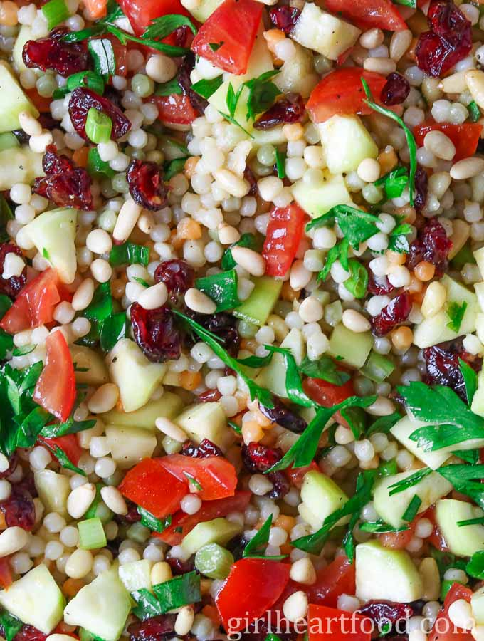 A close up shot of a pearl couscous salad recipe garnished with lots of fresh parsley.
