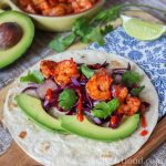 Shrimp taco with garnish on a flour tortilla next to a lime wedge.