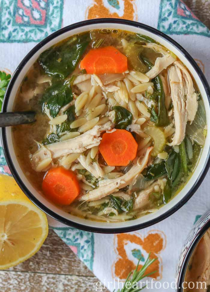 An overhead shot of a bowl of easy lemon chicken orzo soup with spinach alongside a cut lemon.