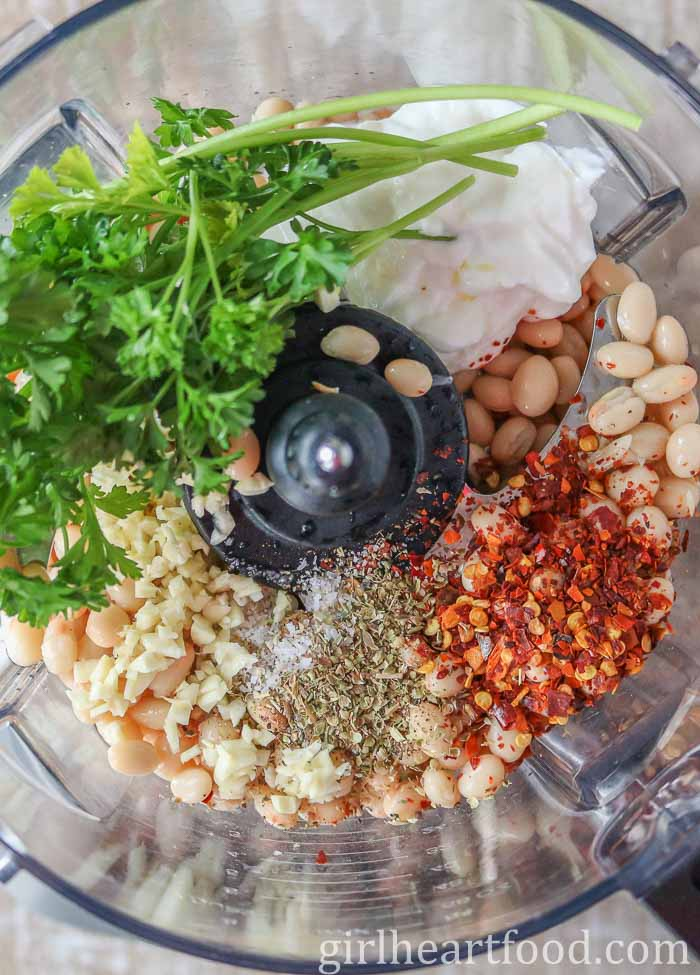 An overhead shot of ingredients for healthy white bean dip in a food processor ready to be blitzed.