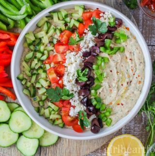An overhead shot of a navy bean dip recipe surrounded by veggies and garnish.