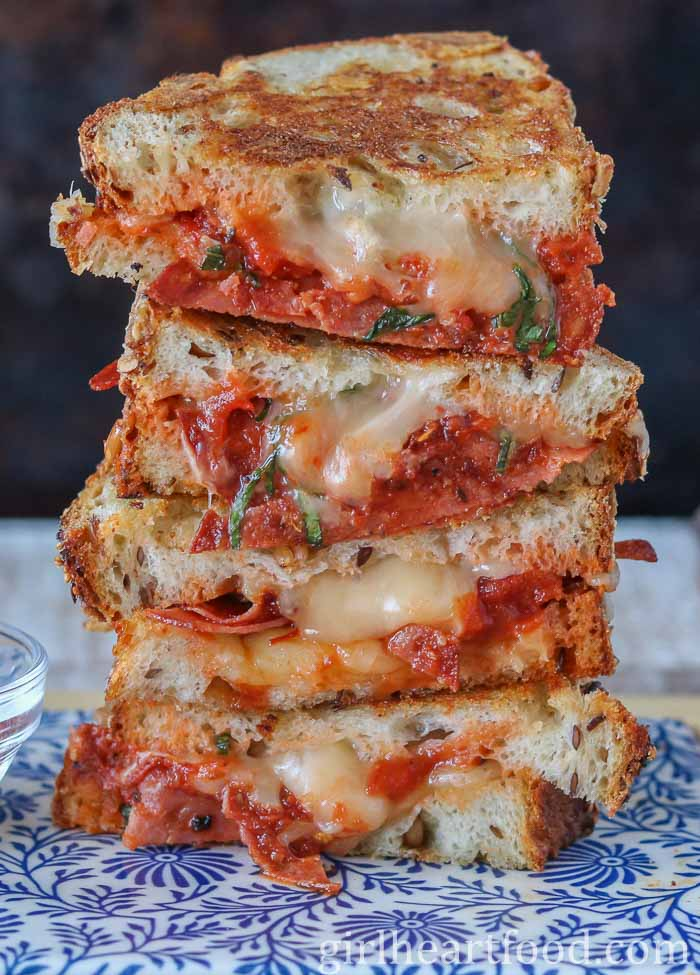 Stack of four pizza grilled cheese sandwich halves.