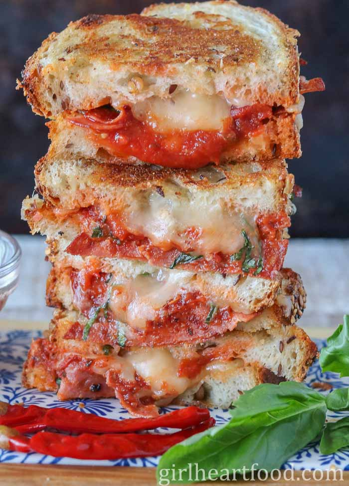 A pizza grilled cheese sandwich stacked high alongside chili and basil.